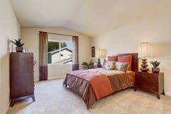 Dormitorio hermoso con lecho anaranjado brillante Imagen de archivo