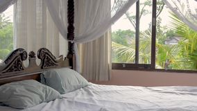 Dormitorio hermoso con una cama de la cama imperial en un alquiler privado de lujo del chalet del día de fiesta en selva tropical almacen de metraje de vídeo