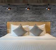 Dormitorio hermoso interior con la pared de ladrillo decorativa de la piedra del granito Foto de archivo