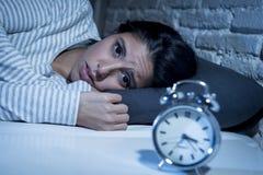Dormitorio hispánico de la mujer en casa que miente en cama tarde en la noche que intenta dormir insomnio sufridor Imagenes de archivo