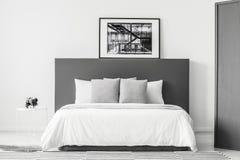 Dormitorio mínimo blanco y gris imagen de archivo