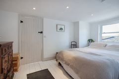 Dormitorio minimalista de la cabaña adornado en blanco Imágenes de archivo libres de regalías