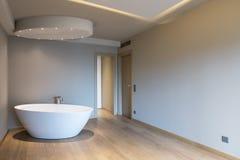 Dormitorio moderno con la bañera, apartamento de lujo foto de archivo