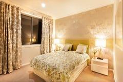 Dormitorio moderno con la cama gigante iluminada por las lámparas de mesa Fotos de archivo libres de regalías