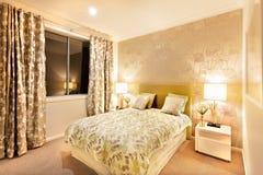 Dormitorio moderno con la cama gigante iluminada por las lámparas de mesa Imagenes de archivo