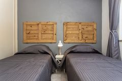 Dormitorio moderno con las almohadas y una cama para los turistas frontal foto de archivo