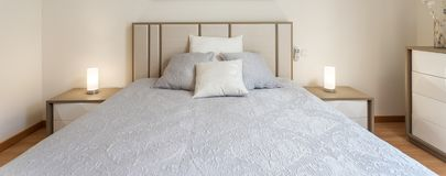 Dormitorio moderno con las almohadas y una cama para los turistas frontal fotografía de archivo libre de regalías