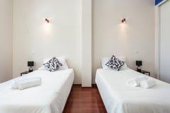 Dormitorio moderno con las almohadas y una cama para los turistas frontal fotografía de archivo