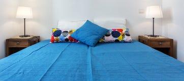 Dormitorio moderno con las almohadas y una cama para los turistas frontal foto de archivo libre de regalías