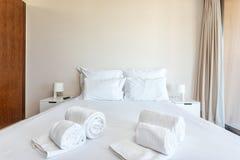 Dormitorio moderno con las almohadas y una cama para los turistas frontal imagenes de archivo