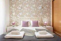 Dormitorio moderno con las almohadas y una cama para los turistas frontal imagen de archivo libre de regalías