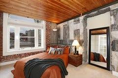 Dormitorio moderno con un muro de cemento quebrado Foto de archivo libre de regalías