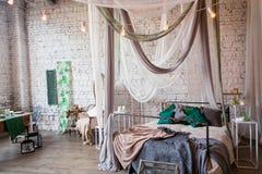 Dormitorio moderno del desván con el alto techo, pared de ladrillo, piso de madera, gabinete de madera, accesorios del diseño en  Foto de archivo