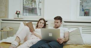 Dormitorio moderno en la señora joven del primer de la mañana que lee un libro en la cama y su socio que miran algo en almacen de video