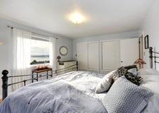 Dormitorio pasado de moda con la cama del marco del hierro Imagen de archivo libre de regalías