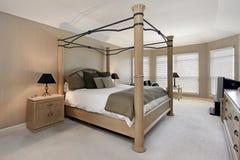 Dormitorio principal con el marco de la cama de madera de roble Foto de archivo libre de regalías