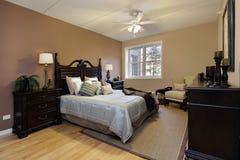 Dormitorio principal con muebles de madera oscuros Imagen de archivo