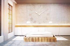 Dormitorio principal con una cama matrimonial, un reloj y dos lámparas, entonados Fotografía de archivo