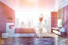 Dormitorio rojo con vista lateral de la TV, mujer imagenes de archivo