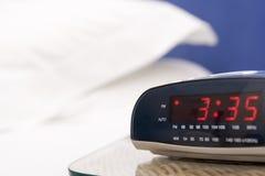 Dormitorio vacío con el foco en el reloj de alarma Imagen de archivo