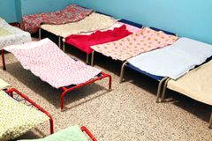 Dormitory with small beds to sleep nursery children Stock Photos