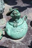 Dormouse in jade colored brass  teapot. Dormouse in jade colored brass teapot part of Alice in Wonderland set Stock Photo