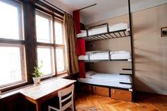 Dormrum av det billiga vandrarhemmet med jämna sängar Arkivbild