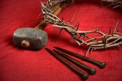 Dornenkrone Nägeln und Hammer auf rotem Stoff Stockfotografie