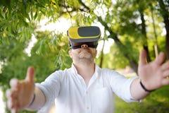 Dorośleć mężczyzny używa rzeczywistości wirtualnej słuchawki plenerową VR, VR szkła, zwiększający rzeczywistości doświadczenie zdjęcie stock