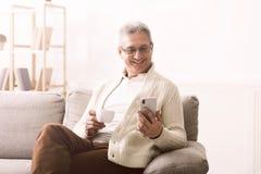 Dorośleć mężczyzny używa smartphone i pijący kawę fotografia stock