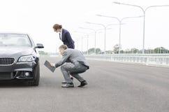 Dorośleć asekuracyjnego agenta analizuje awaria samochód przeciw niebu podczas gdy bizneswoman pozycja na drodze obraz royalty free