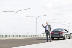 Dorośleć biznesmena hitchhiking podczas gdy stojący z awaria samochodem na drodze zdjęcie stock