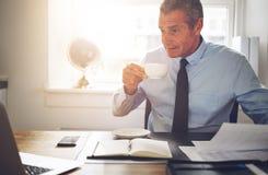 Dorośleć biznesmena pije kawę podczas gdy pracujący przy jego biurowy d fotografia stock