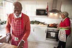 Dorośleć czarnej pary przygotowywa Bożenarodzeniowego gościa restauracji, mężczyzny ciapania warzywa w przedpolu fotografia royalty free