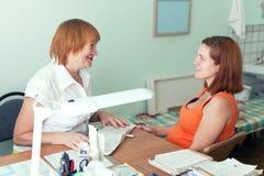 Dorośleć lekarkę egzamininuje kobieta w ciąży obrazy stock