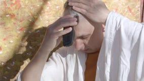 Dorośleć mężczyzna ciie jego włosy z elektryczną żyletką, siedzieć plenerowy zbiory