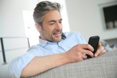 Dorośleć mężczyzna dosłania sms z smartphone zdjęcie royalty free