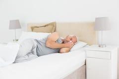 Dorośleć mężczyzna dosypianie w łóżku Fotografia Stock