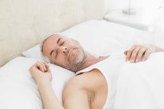 Dorośleć mężczyzna dosypianie w łóżku w domu Obraz Royalty Free