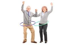 Dorośleć mężczyzna i kobiety ćwiczy z hula obręczem Fotografia Royalty Free