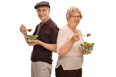 Dorośleć mężczyzna i kobiety łasowania sałatki Zdjęcie Stock