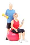 Dorośleć mężczyzna i kobiety pozuje z ćwiczyć wyposażenie Fotografia Stock