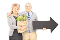 Dorośleć mężczyzna i kobiety trzyma dużego czarnego strzałkowatego wskazywać i torbę Zdjęcie Royalty Free