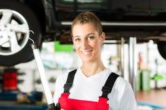 Dorośleć mężczyzna i w warsztacie żeńskiego samochodowego mechanika Obraz Royalty Free