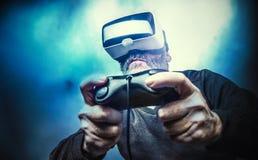 Dorośleć mężczyzna jest ubranym rzeczywistość wirtualna gogle/VR szkła bawić się Obraz Royalty Free