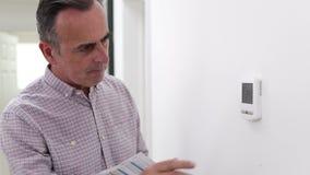 Dorośleć mężczyzna obraca puszka środkowego ogrzewania cieplarkę z rachunkiem zbiory wideo