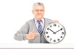 Dorośleć mężczyzna obsiadanie i wskazywać na ściennym zegarze Zdjęcie Royalty Free