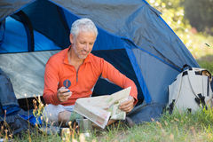 Dorośleć mężczyzna patrzeje mapę i trzyma kompas Fotografia Royalty Free