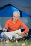 Dorośleć mężczyzna patrzeje mapę i trzyma kompas Obraz Royalty Free