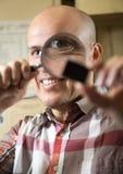 Dorośleć mężczyzna patrzeje przez powiększać - szkło na rzeczy Obrazy Royalty Free